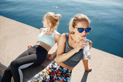 Runner woman drinking water on beach with asian friend running Royalty Free Stock Photography