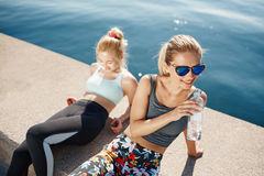 Runner woman drinking water on beach with asian friend running Royalty Free Stock Image