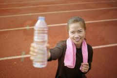 Runner woman drinking water while exercises. On the training at stadium Stock Photography