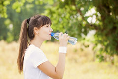 Runner woman drinking water after jogging Royalty Free Stock Photo