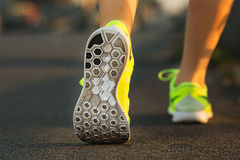 Runner woman feet running on road closeup on shoe. Female fitness model sunrise jog workout. Sports lifestyle concept.