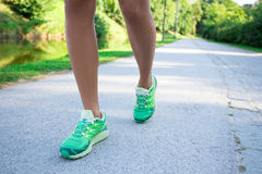 Runner woman feet running on road in park. Runner woman feet running on road in summer park Royalty Free Stock Images