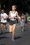 Runner woman foreground and several runners in background Royalty Free Stock Image