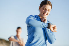 Runner woman with heart rate monitor running on beach Royalty Free Stock Photos