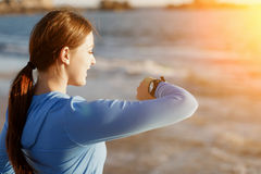 Runner woman with heart rate monitor running on beach Royalty Free Stock Image