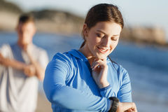 Runner woman with heart rate monitor running on beach Stock Photo