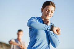 Runner woman with heart rate monitor running on beach Royalty Free Stock Photo