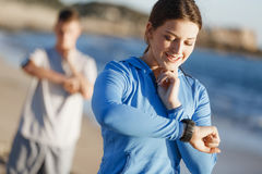 Runner woman with heart rate monitor running on beach Stock Image