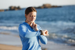 Runner woman with heart rate monitor running on beach Stock Photos