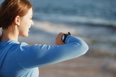 Runner woman with heart rate monitor running on beach Stock Images