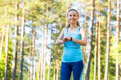 Runner woman with heart rate monitor for running in forest. Stock Images
