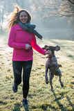 Runner woman and her cute German pointer dog running together Stock Photos