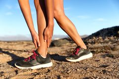 Sprained ankle running injury athlete runner woman. Runner woman with hurt ankles in pain during marathon. Athlete woman running outside with body injury royalty free stock photos