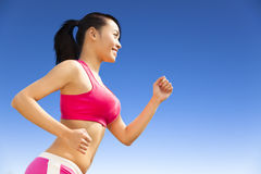 Runner woman jogging in sunny day. Smiling runner woman jogging in sunny day outdoors royalty free stock photography