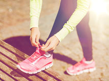 Runner woman lacing trainers shoes. Sport, fitness, exercise and lifestyle concept - runner woman lacing trainers shoes Stock Image