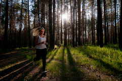 The runner woman on path in forest against the sun Stock Photo