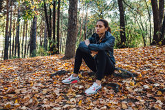 Runner woman rest on the leaves in park Stock Image