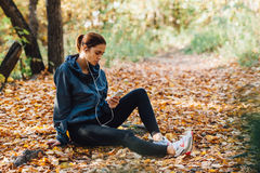 Runner woman rest on the leaves in park Stock Photography