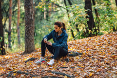 Runner woman rest on the leaves in park Royalty Free Stock Photography