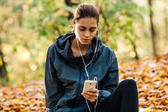 Runner woman rest on the leaves in park Stock Images