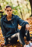 Runner woman rest on the leaves in park Royalty Free Stock Image