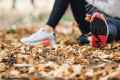 Runner woman rest on the leaves in park Royalty Free Stock Photo