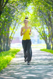 Runner - woman running outdoors in green park Stock Photography