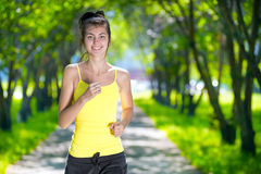 Runner - woman running outdoors in green park Royalty Free Stock Image