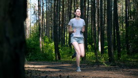 Runner woman running in park exercising outdoors fitness tracker wearable technology girl running in the woods in the