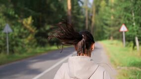 Runner woman running in park. Female jogger running on road and street in park with trees. Runner doing outdoor cardio
