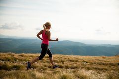 Runner - woman runs cros country on a path in early autumn.  Stock Image