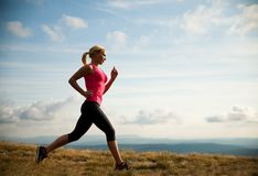 Runner - woman runs cros country on a path in early autumn Stock Images
