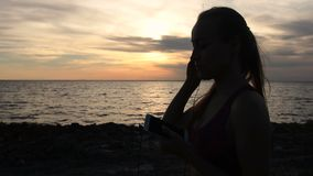 Runner woman setting music on smartphone at sunset stock video