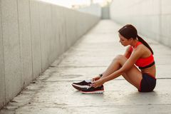Runner woman sitting on the ground and tie laces Royalty Free Stock Photo