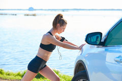 Runner woman stretching on a car in the lake Royalty Free Stock Photo