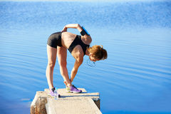 Runner woman stretching in a lake outdoor Royalty Free Stock Photography