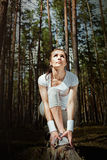 Runner woman stretching thigh before running in forest and looking to the sky. Stock Photos