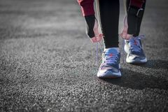 The Runner woman ties the shoelaces before running. Healthy life. Style Royalty Free Stock Photos