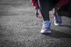 The Runner woman ties the shoelaces before running. Healthy life. Style Stock Photos