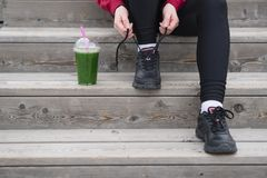 The Runner woman ties the shoelaces before running. Healthy life. Style. Detox smoothie Royalty Free Stock Images