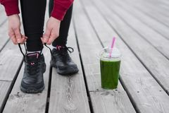 The Runner woman ties the shoelaces before running. Healthy life. Style. Detox smoothie Royalty Free Stock Photos