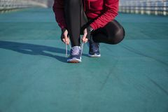 The Runner woman ties the shoelaces before running. Healthy life. Style Royalty Free Stock Photo