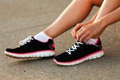 Runner woman tying laces closeup Stock Photos