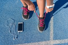 Runner tying running shoes laces on race run track. Runner woman tying running shoes laces getting ready for race on run track with smartphone and earphones for stock photos