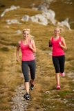 Runner - woman runs cros country on a path in early autumn. Runner - women runs cros country on a path in early autumn Stock Images