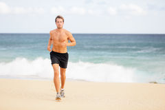 Runner - Young man jogging on the beach. Runner. Athletic young man jogging and running on the beach shirtless in sport shorts running towards the camera in Stock Photography