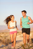 Runners - Active fitness couple running laughing Stock Images