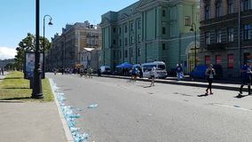 Runners athletes run a marathon through the streets of the metropolis. On the roadside discarded water bottles stock video footage