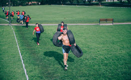 Runners carrying tires in a test of extreme obstacle race Stock Images