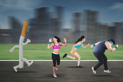 Runners chased by a cigarette Stock Photography